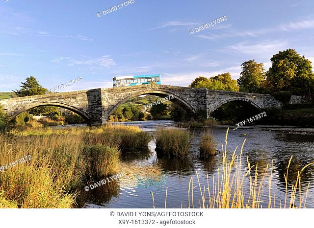 Arriva bus crosses the River Conwy on the Pont Fawr bridge in the old town of Llanrwst in the Conwy Valley, Gwynedd, Wales, UK