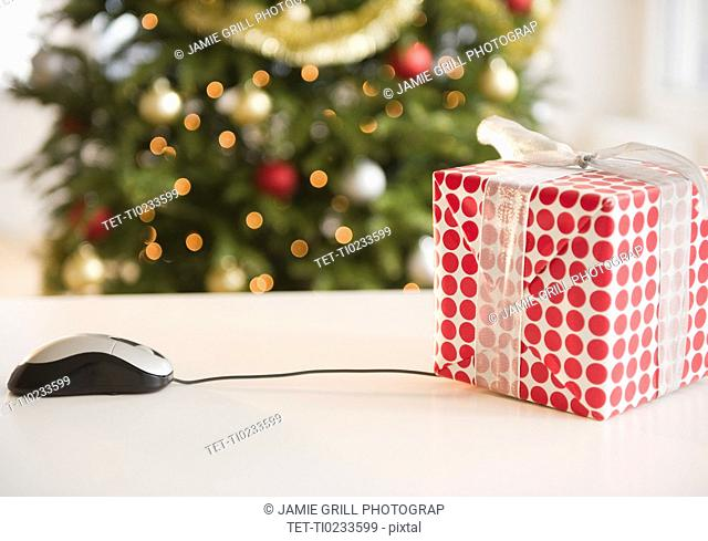 Computer mouse connected to Christmas gift