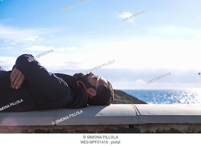 Man relaxing on a wall