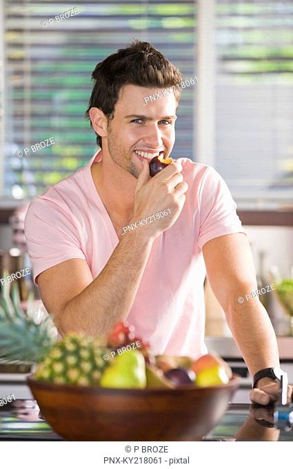 Portrait of a man eating a nectarine