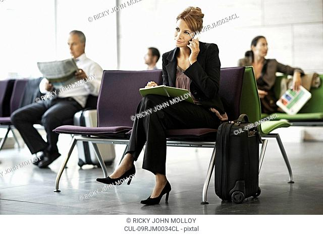 Woman with suitcase, on the phone