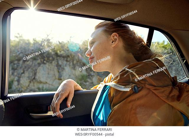 Young woman in a car looking out of window