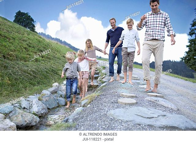 Father And Children On Countryside Path Next To Stream