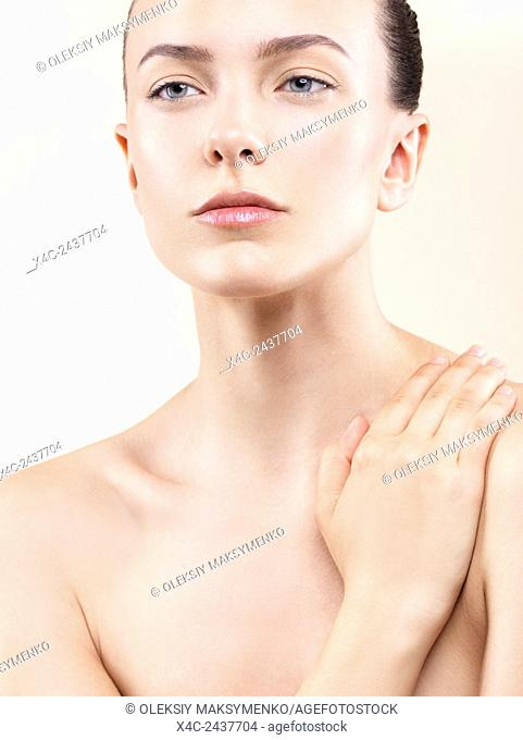 Beauty portrait of a young woman with clean natural look and perfect skin on beige background