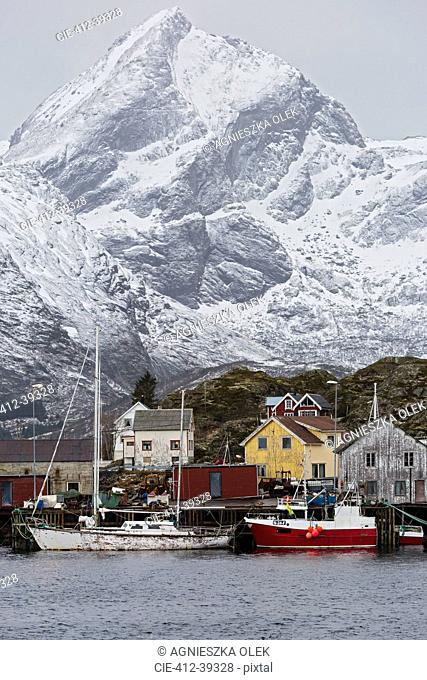 Fishing village and boats at waterfront below snowy, rugged mountains, Sund, Lofoten, Norway