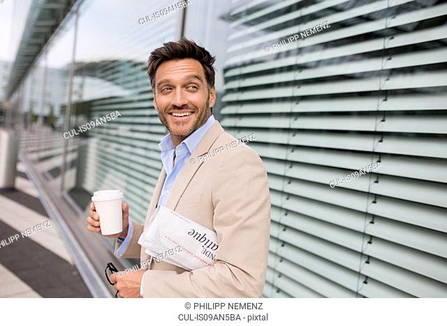 Mature businessman walking outside city office carrying takeaway coffee
