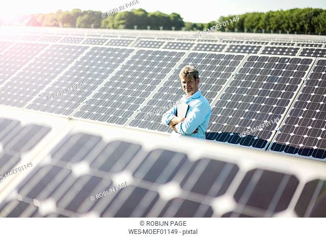 Mature man with laptop standing in solar plant