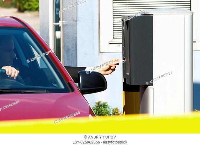 Man Sitting In Car Inserting Ticket For Parking Area
