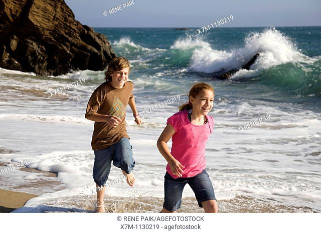 A boy playfully chases a young girl on a beach in Santa Cruz, California