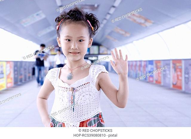Portrait of a girl standing in a corridor and waving her hand