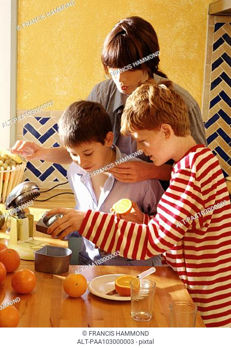 Woman and children looking at juicer