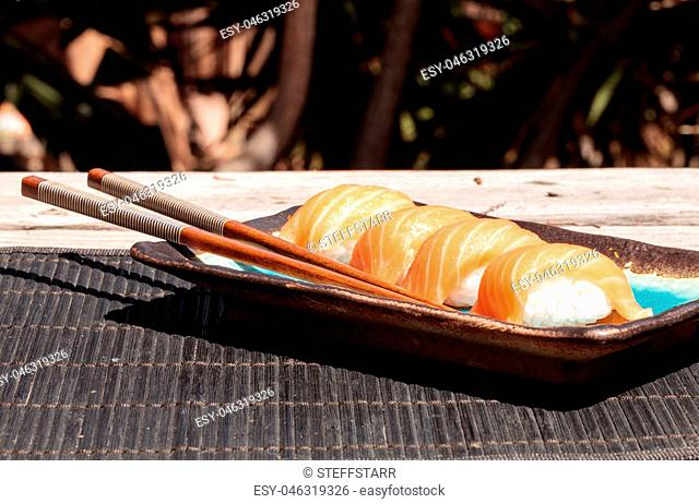 A meal of salmon sushi on white rice on a blue plate with chopsticks