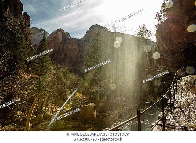 Sunlight flares in the lens looking onto a mountain landscape scene in Zion National Park