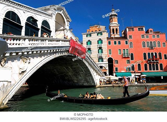 Gondolier with three persons paddling under the Rialto Bridge, Italy, Venice