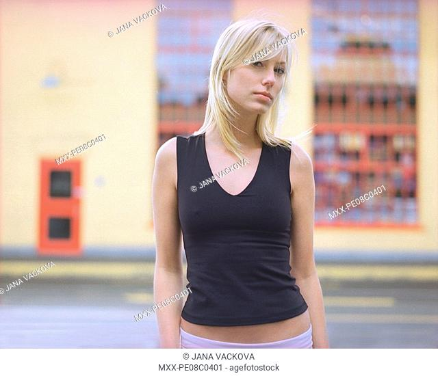 Woman standing on street infront of building