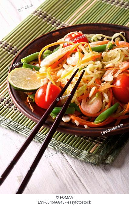 Papaya salad som tam with shrimp close-up on a plate on the table. Vertical
