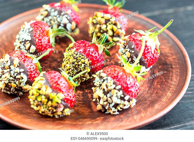 Fresh strawberries covered with dark chocolate and nuts