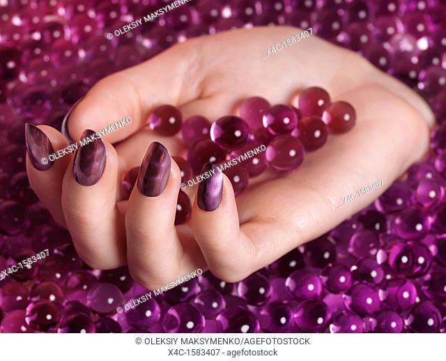 Closeup of woman's hand with purple nail polish coming out of a pile of pink candy