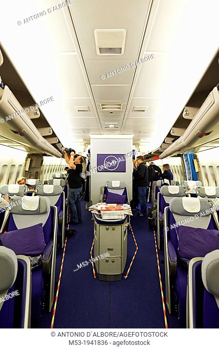 Interior view of the lower deck of an Airbus A380 jet airliner owned by the german airlines Lufthansa. Passengers are just boarding and putting their handbags...