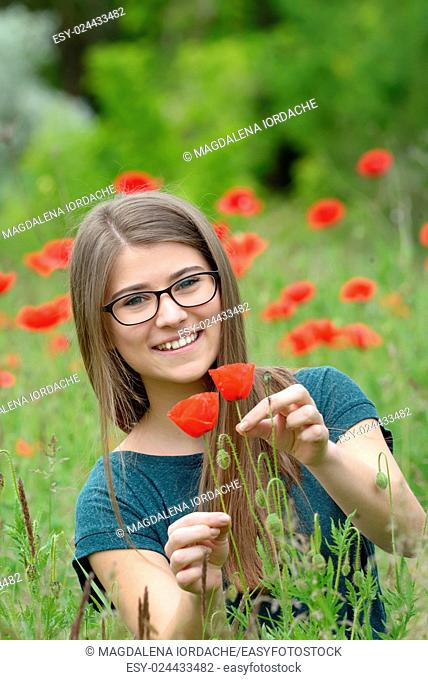 Portrait of young girl with poppy flowers in nature