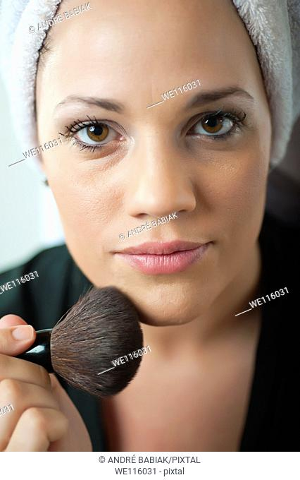 Close up of woman's face putting on makeup
