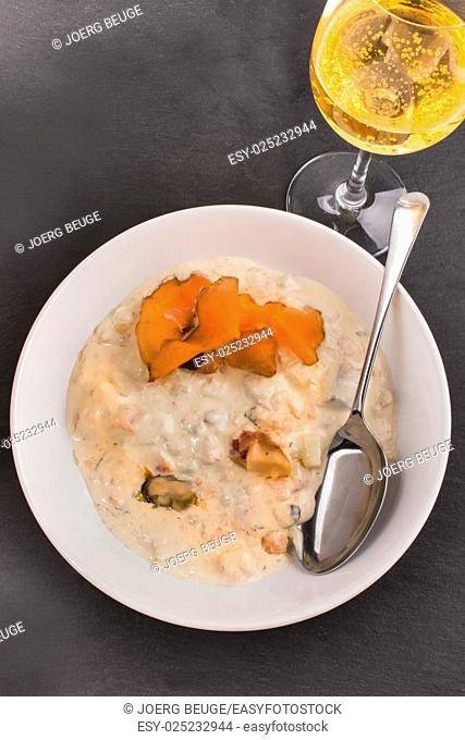 scottish seafood chowder in a deep plate and apple cider in a glass