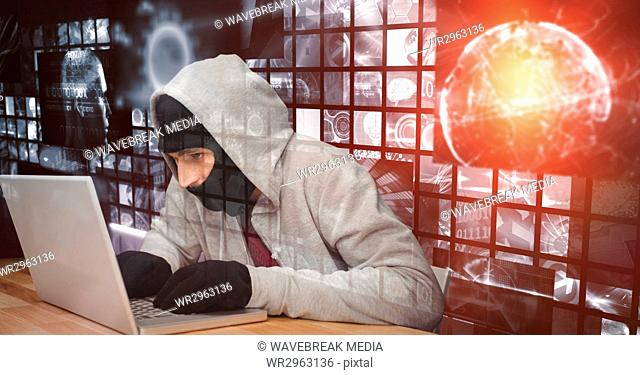 Digital composite image of hacker using laptop at desk