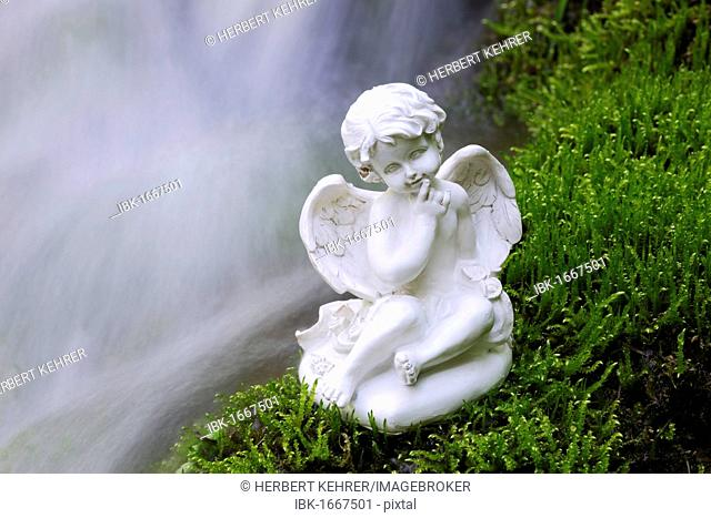Porcelain angel figure on moss at a waterfall