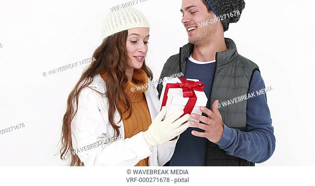 Casual couple in warm clothing holding gift