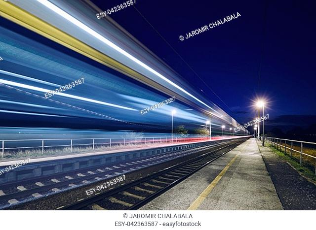 Light trails of passenger train commuting to railroad station at night