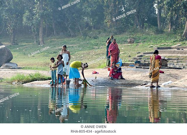 Women washing clothes on the ghats of the River Mahanadi, reflected in the water, Orissa, India, Asia