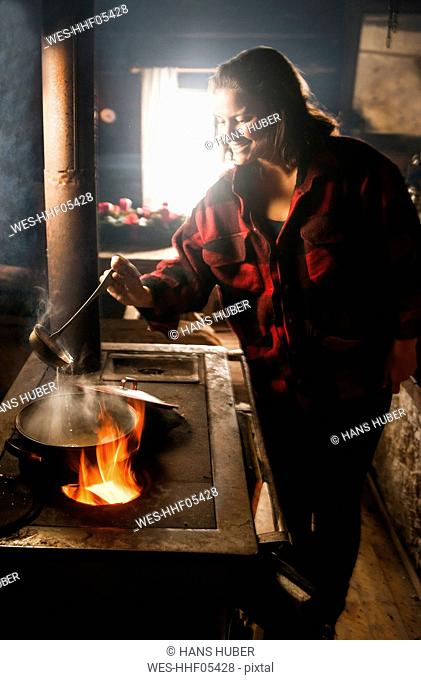 Woman cooking on furnace in a wooden hut