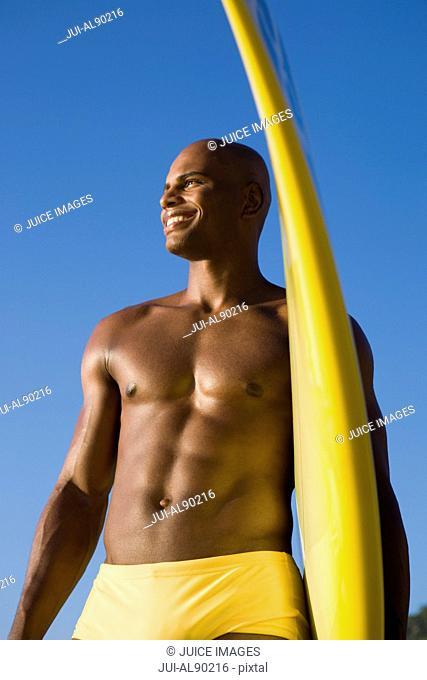 African man holding surfboard