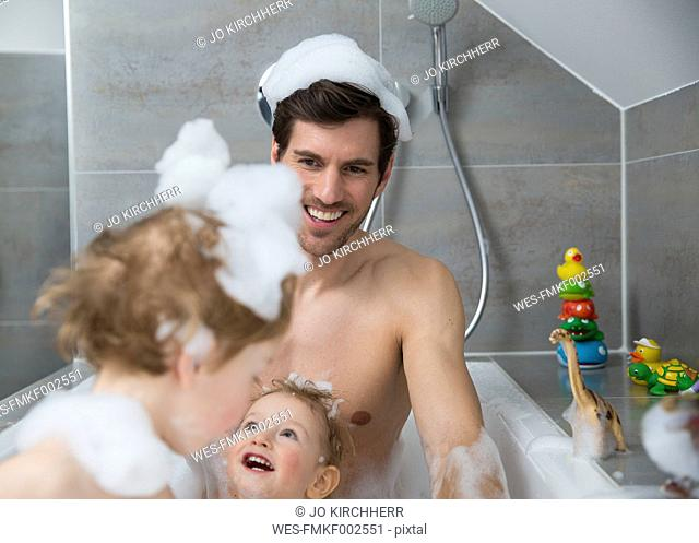 Father having fun with sons in bathtub