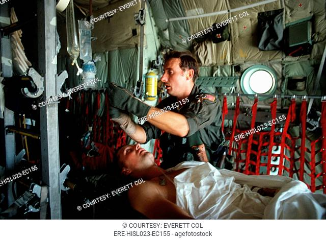 A medic adjusts the intravenous drip bag of a wounded US serviceman en route to a medical facility after the invasion of Grenada