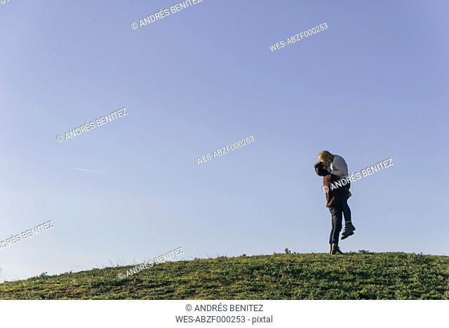 Young couple kissing on a hill in front of blue sky
