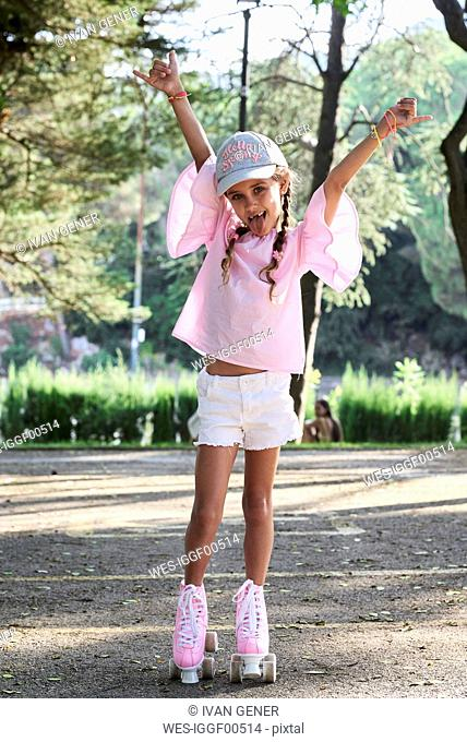 Happy little girl raising arms while roller skating in a park