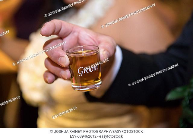 Specialized custom shot glass full of whiskey has groom on it for the bridegroom to use during toasts at his wedding reception