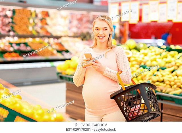 technology, shopping, food, pregnancy and people concept - happy pregnant woman with basket and smartphone at grocery store or supermarket