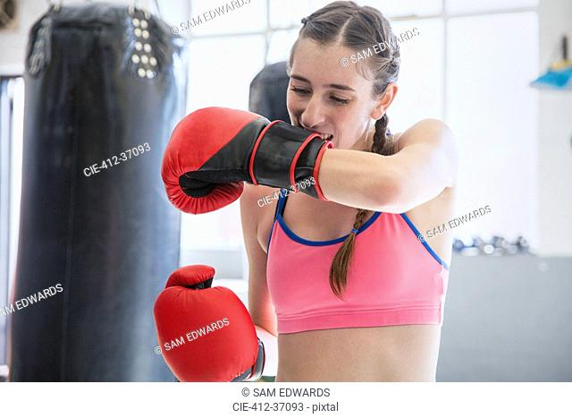Young female boxer biting, removing boxing gloves at punching bag in gym