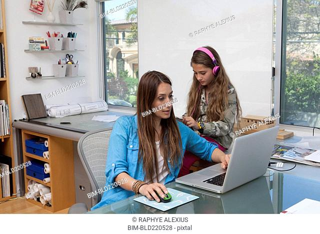 Mixed race mother and daughter talking in home office