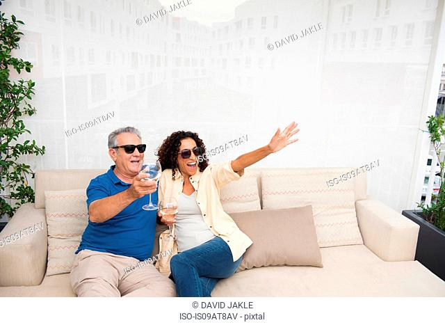Senior man and wife waving from patio sofa