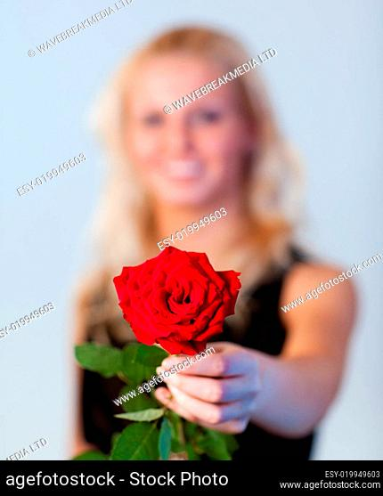 Young woman holding a rose with focus on rose