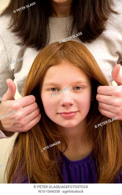 Mother fixing the hair of her preteen redhead daughter