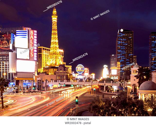 View along the Strip in Las Vegas at night, with the illuminated Paris Las Vegas Hotel and Casino in the background