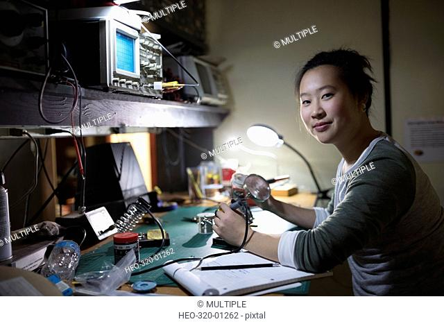 Portrait female engineer using soldering iron assembling electronic components in workshop