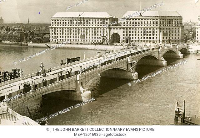 The new Lambeth Bridge across the River Thames, shortly before it was opened, 19 July 1932. On the opposite bank is the Grade II listed Thames House