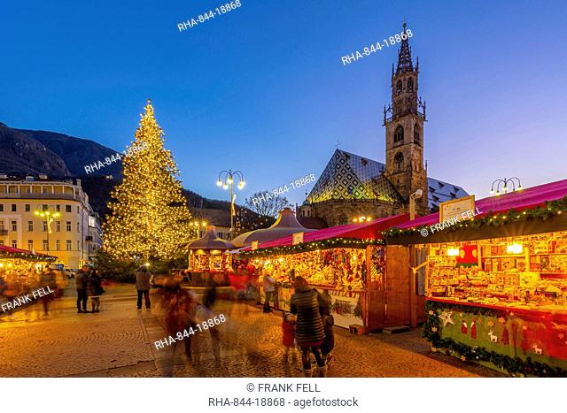 Bolzano Cathedral and long exposure of customers at Christmas Market in Piazza Walther, Bolzano, Italy, Europe