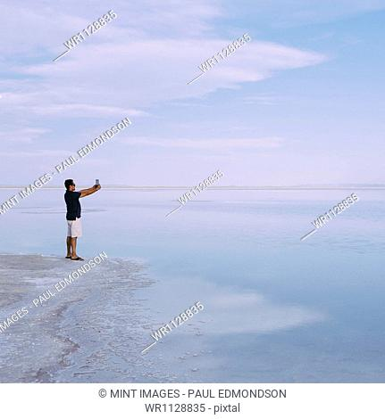 A man standing at edge of the flooded Bonneville Salt Flats at dusk, taking a photograph with a tablet device, near Wendover