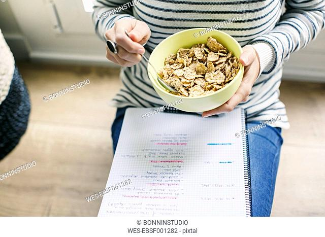 Woman sitting on floor with muesli bowl and notepad
